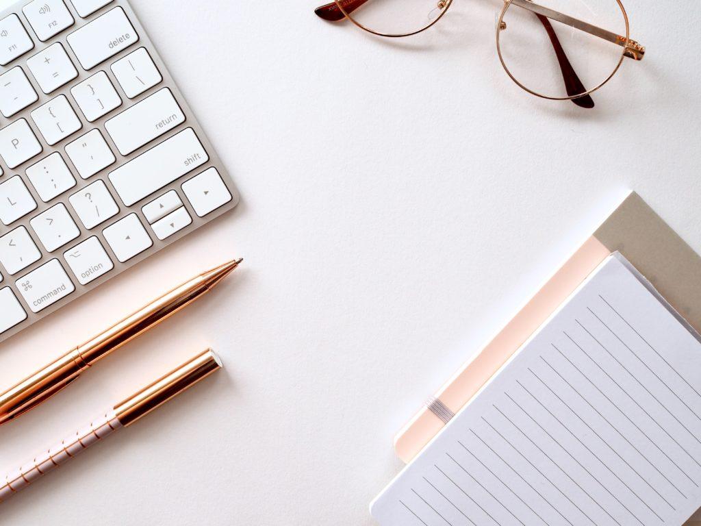 Arbeitsplatz mit Tastatur, Brille und Notizbüchern